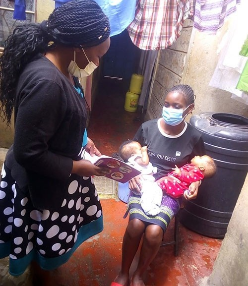 Three months later, Community Health Worker Florence Nthenya visit Lavender Atieno at her house in Kayole to check on her infant's progress following Kangaroo Mother Care.