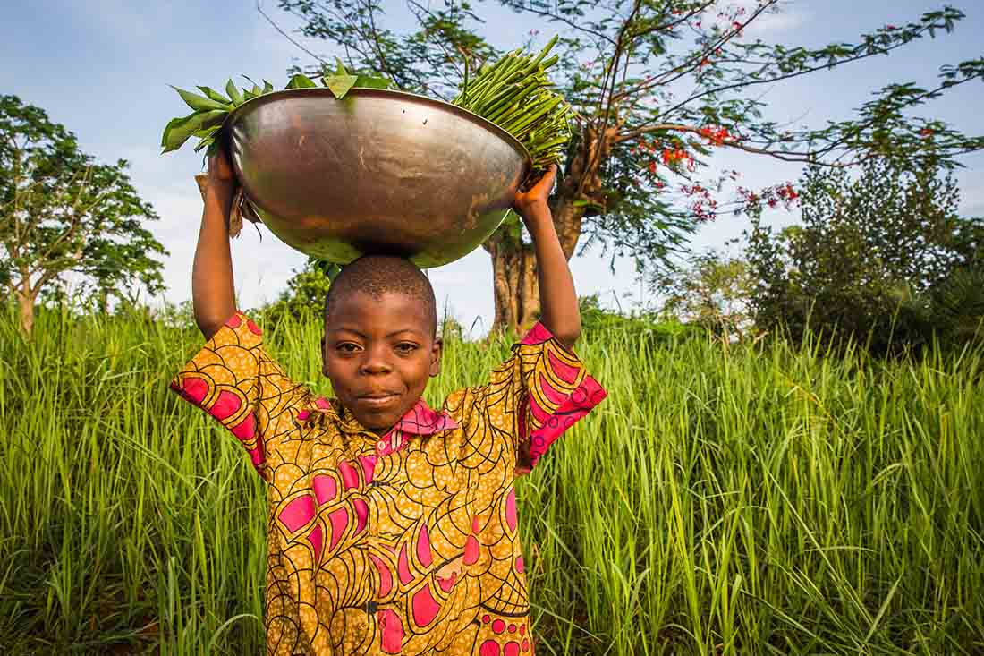 A child carries a bowl filled with leafy greens in Gbado in the Democratic Republic of Congo, where IMA World Health works to improve health, healing and well-being for nearly 9 million people. (Photo by Crystal Stafford/IMA World Health)