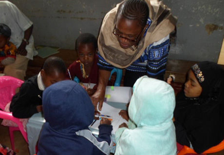 Levina Swai, CTC Medical Officer In-Charge, helps children write during the Children's Clinic