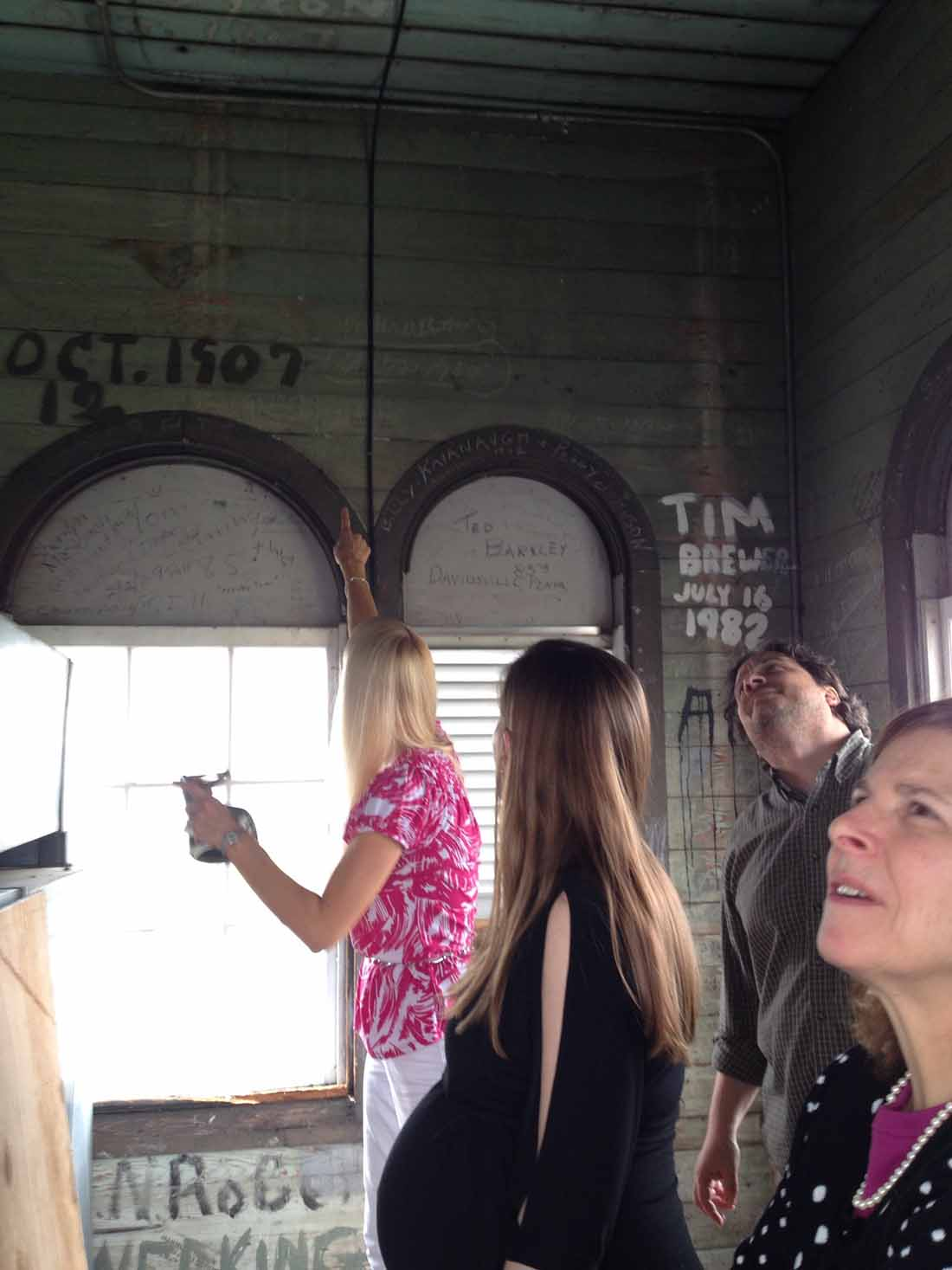 Sherry Chastain, Emily Esworthy, Ryan Williams and Carol Shores read the writing on the walls of the cupola of Old Main.