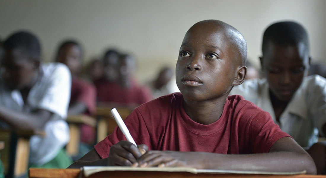 Samweli Hassani listens during class in his school in Fela, Tanzania. The 14-year-old boy was diagnosed with Burkitt's Lymphoma, an aggressive childhood cancer that causes disfiguring tumors and can be fatal within weeks if not treated. Fortunately, his mother was able to get him to a clinic quickly. He received treatment and beat BL. (IMA World Health/Paul Jeffrey)
