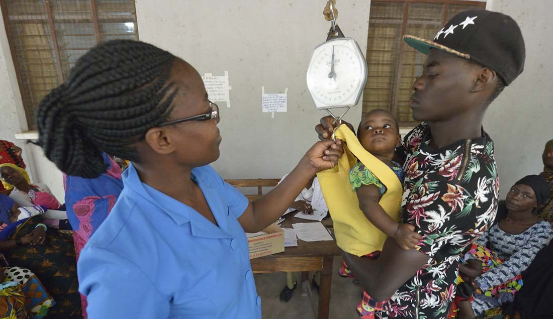 Nurse Praxeda Kahwa helps Jumanne Kessy hoist his daughter Esther onto a scale in the Nyamagana District Hospital in Mwanza, Tanzania. The child and others were weighed as part of a nutrition screening program at the hospital. (Photo by Paul Jeffrey)