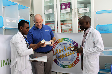 Luke King, IMA's Country Director in Tanzania, center, looks at chemotherapy drugs with pharmacists at Muhimbili National Hospital in Dar es Salaam, Tanzania. (Jennifer Bentzel/IMA World Health)