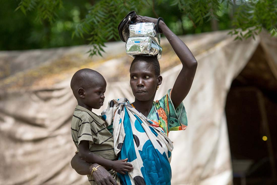 "A mother and child exit the John Dau Foundation compound with bags of Super Cereal Plus-- a highly fortified food supplement for children-- in Duk Padiet in South Sudan's Jonglei state, September 29, 2017. Lutheran World Relief has partnered with IMA World Health and in turn, the John Dau Foundation, to set up and run three life-saving medical stabilization centers, including one that will be installed on this site, for the treatment of young children and lactating mothers at risk of death from starvation. The project, called ""Providing Emergency Nutrition Services in South Sudan"" will reach just under 100,000 individuals. (photo by Allison Shelley for Lutheran World Relief)"