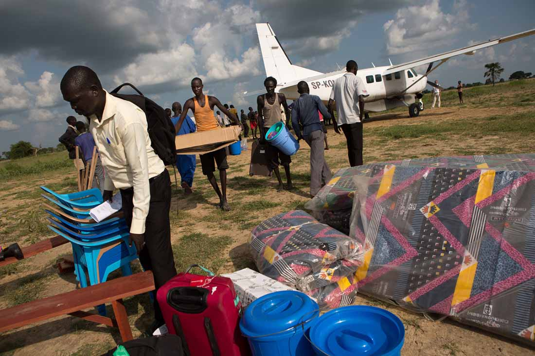 "A team unloads LWR-provided medical center supplies at the dirt airstrip in Duk Padiet, in South Sudan's Jonglei state, September 27, 2017. Small charter flights are often the only way to get supplies to remote villages in the rainy season, when the dirt roads that connect them become impassibly muddy. Lutheran World Relief has partnered with IMA World Health and in turn, the John Dau Foundation, to set up and run three life-saving medical stabilization centers, including in Duk Padiet, to treat young children and lactating mothers at risk of death from starvation. The project, called ""Providing Emergency Nutrition Services in South Sudan"" will reach just under 100,000 individuals. (photo by Allison Shelley for Lutheran World Relief)"