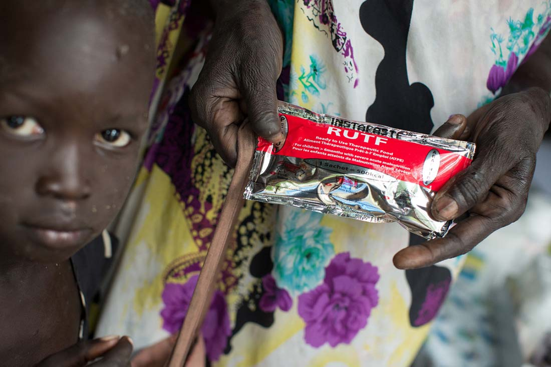 "A mother and child receive packets of ""Ready-to-Use Therapeutic Food""-- a vitamin and mineral fortified peanut paste mixed with dry milk given to malnourished children-- at the John Dau Foundation compound in Duk Padiet in South Sudan's Jonglei state, September 29, 2017. Lutheran World Relief has partnered with IMA World Health and in turn, the John Dau Foundation, to set up and run three life-saving medical stabilization centers, including one that will be installed on this site, for the treatment of young children and lactating mothers at risk of death from starvation. The project, called ""Providing Emergency Nutrition Services in South Sudan"" will reach just under 100,000 individuals. (photo by Allison Shelley for Lutheran World Relief)"