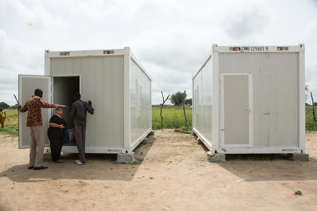 """Local staff show Nancy McGaughey, a reproductive health and nutrition advisor with IMA World Health, their just-delivered medical stabilization center units at an IMA World Health clinic site in Duk Payuel in South Sudan's Jonglei state, September 30, 2017. Lutheran World Relief has partnered with IMA World Health to set up and run three life-saving medical stabilization centers identical to this one to treat young children and lactating mothers at risk of death from starvation in the region. The project, called """"Providing Emergency Nutrition Services in South Sudan"""" will reach just under 100,000 individuals. (photo by Allison Shelley for Lutheran World Relief)"""