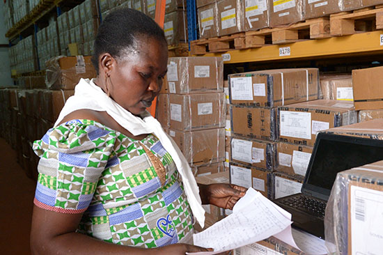 Lily Kaku, of the South Sudan Ministry of Health's Central Medical Store, checks inventory against a spreadsheet in preparation for distributing supplies. (Photo by Matt Hackworth/IMA World Health)