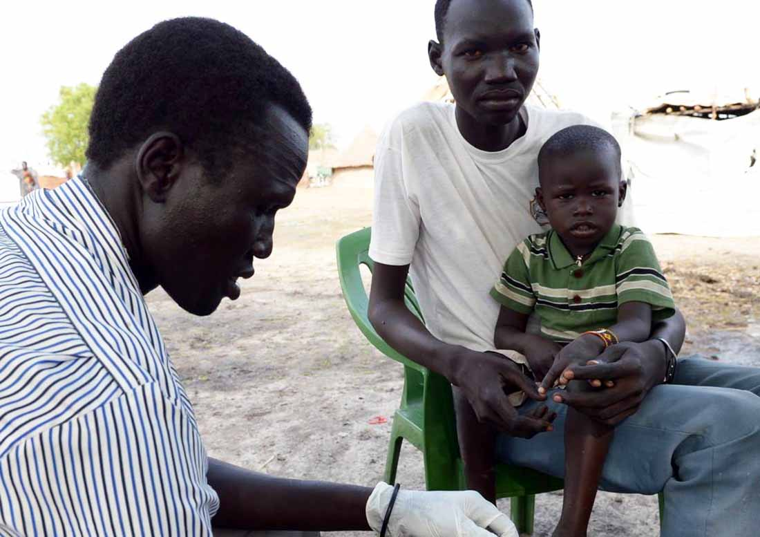 A community health worker in Poktap, South Sudan, tests 3-year-old Abot Dau for malaria while his father Dut Dau looks on. The test was negative. (Photo by Matt Hackworth/IMA World Health)