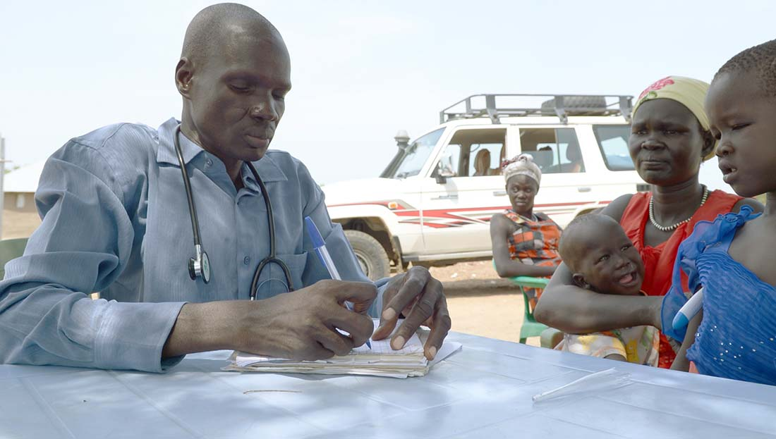 This clinic under a tree serves primarily people displaced by violence. It is operated by Sudan Medical Care and supported by the Rapid Results Health Project. Clinic manager Simon Ateu Chol checks up on the children of mother, Tom Lualo. Chol says the clinic can see as many as 200 patients each day during the rainy season, when malaria cases are most frequent. (Photo by Matt Hackworth/IMA World Health)