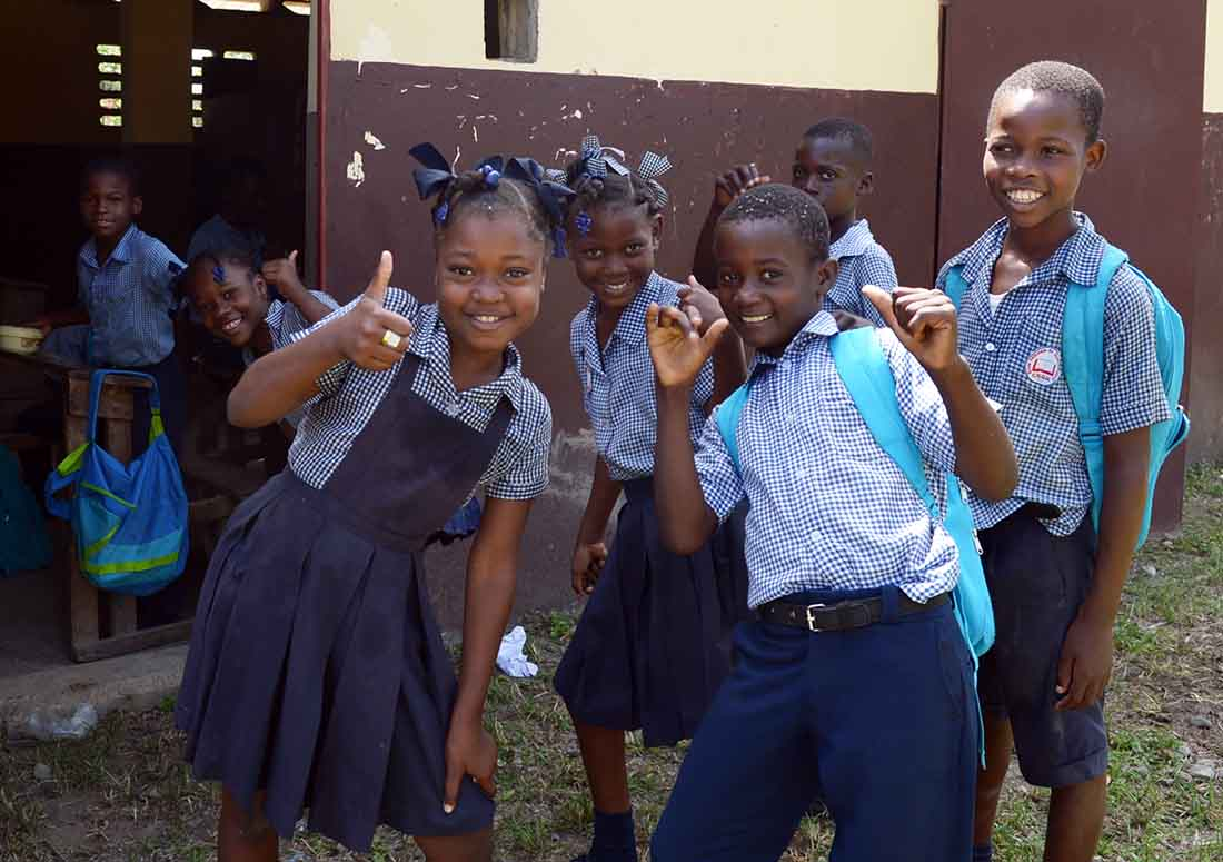 Students at Ecole Nationale de Quartier-Morin give a thumbs up during a mass drug administration at their school on April 19, 2018 in the Nord Department of Haiti. Thousands of community volunteers have been deployed for the Caribbean country's annual MDA of medicine to prevent lymphatic filariasis and soil transmitted helminths. Supporting the Haiti Ministry of Public Health and Population in this effort is the U.S. Agency for International Development, RTI International and IMA World Health. (Photo by Kara Eberle/IMA World Health)