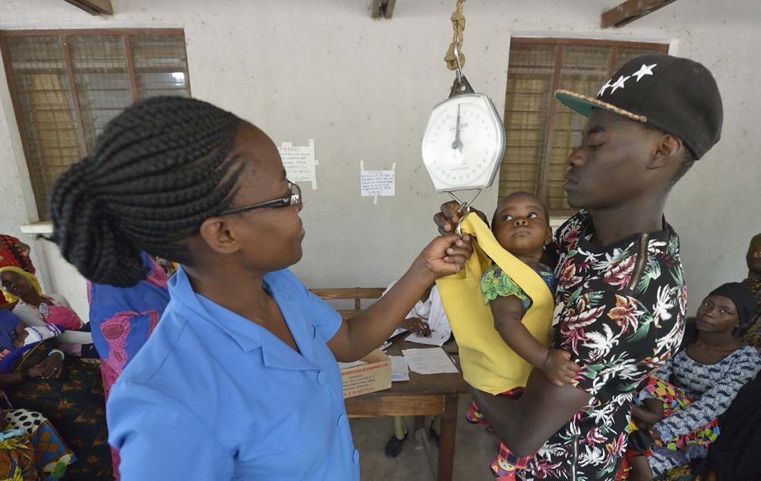 Nurse Praxeda Kahwa helps Jumanne Kessy hoist his daughter Esther onto a scale in the Nyamagana District Hospital in Mwanza Tanzania. The child and others were weighed as part of a nutrition screening program at the hospital. (Photo by Paul Jeffrey/IMA World Health)