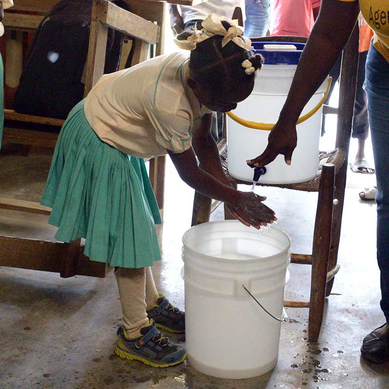 A student at Eglise La Foi Apostolique demonstrates proper hand-washing technique to show what she has learned.