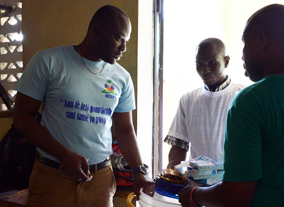 Dr. Victor Cadet, left, head of the cholera program at Haiti's Ministry of Public Health and Population North, assists with distribution of the supplies at Eglise La Foi Apostolique.