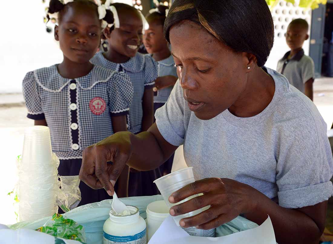 A community health worker prepares to deliver treatment for lymphatic filariasis and soil-transmitted helminths at a school in northern Haiti. (Photo by Kara Eberle/IMA World Health)
