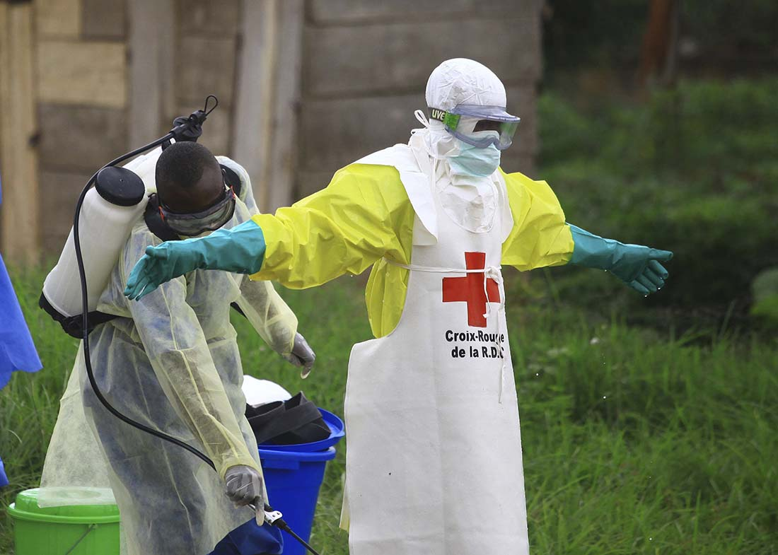 A health worker sprays disinfectant on his colleague after working at an Ebola treatment centre in Beni, Eastern Congo, in early September 2018. (AP Photo/Al-hadji Kudra Maliro)