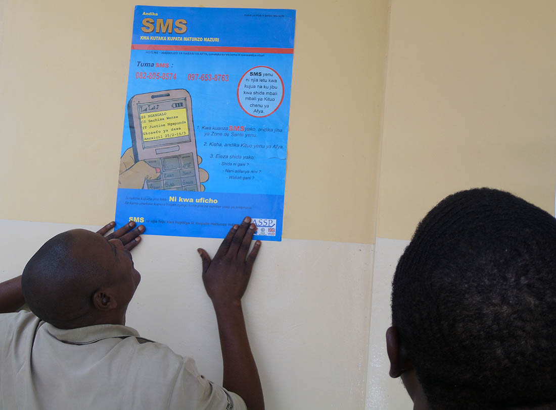 Olivier Cianyi hangs a Hotline poster in the Central Office of the Health Zone in Kindu on August 20, 2018.