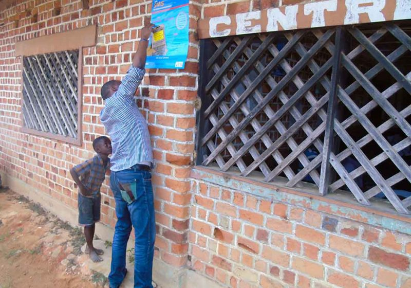 Olivier Cianyi, IMA Hotline Dispatcher, hangs a Hotline poster with the help of a curious onlooker at a health center in Kalima, about 64 miles from Kindu, Maniema, DRC, on August 28, 2018.
