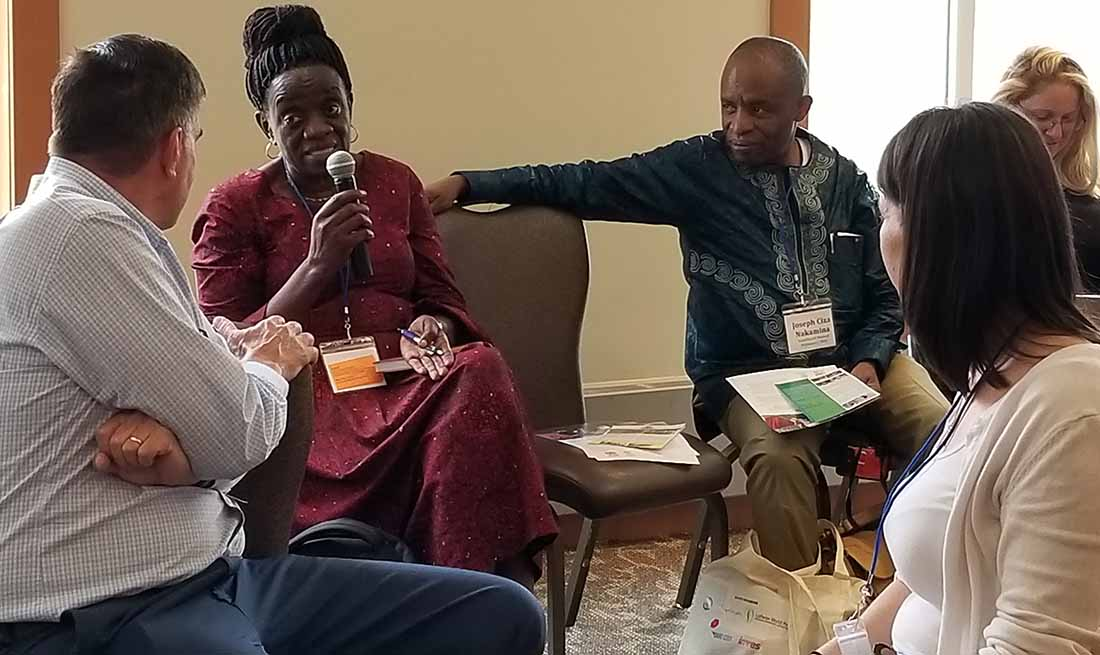Generose Mulokozi, PhD, ASTUTE Team Leader, IMA World Health, speaks as Joseph Ciza, Chief of Party for the USAID Counter Gender-Based Violence Program, IMA World Health, looks on during the CCIH 2019 conference in Baltimore.
