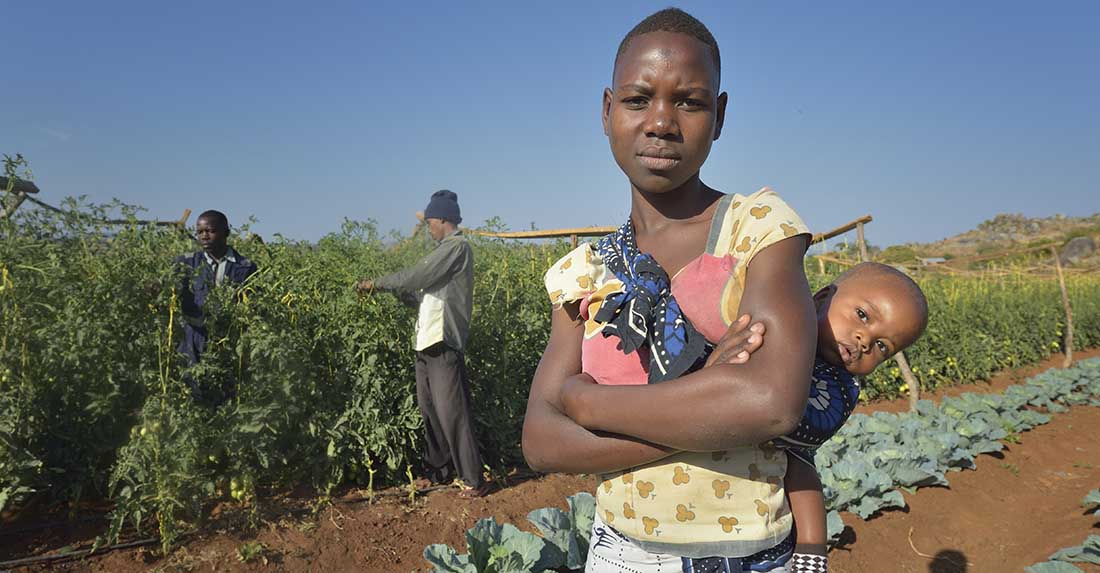 Elizabeth Mwita, with her 10-month old son Samuel, works on a farm in Mwanza, Tanzania. (Photo by Paul Jeffrey/IMA World Health)