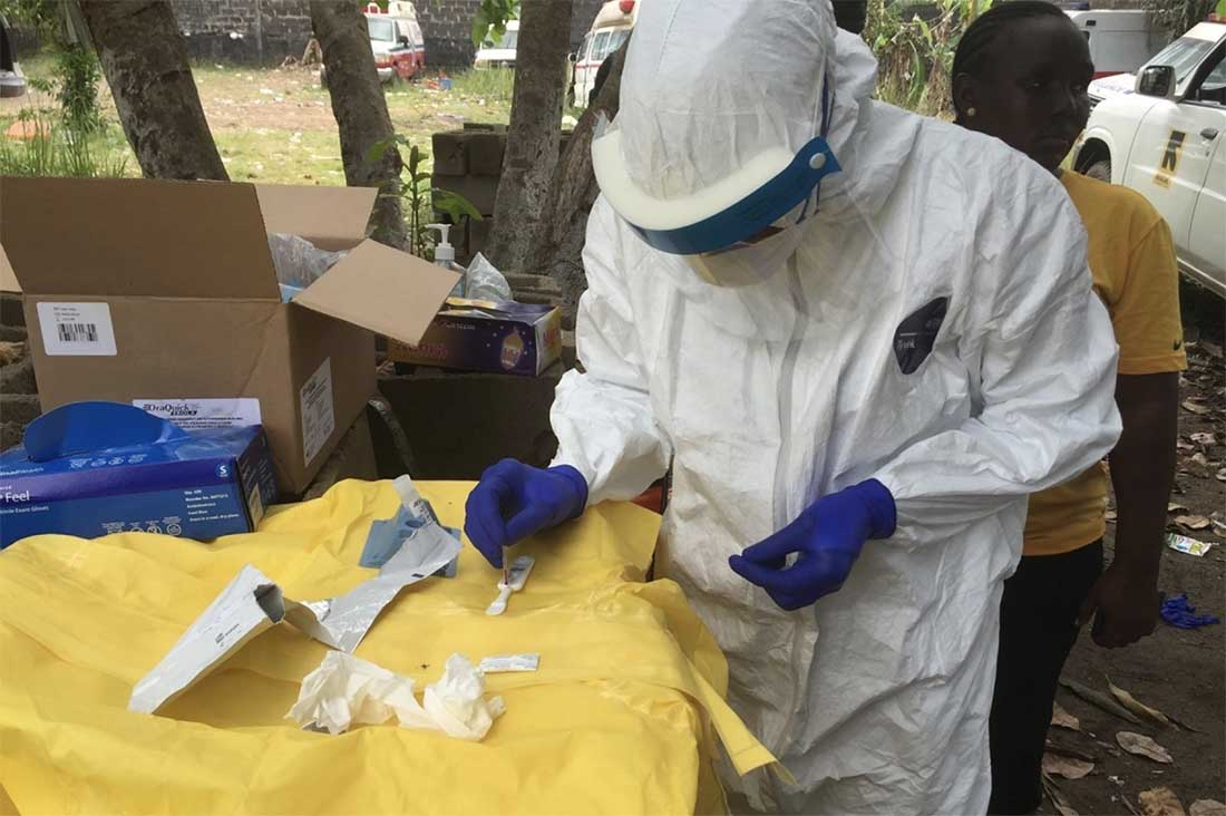 While in the field, dressed in personal protective equipment (PPE), this epidemiologist conducts a rapid diagnostic test, which was used during the Ebola response to quickly test for the presence of Ebola virus. (Photo by John Saindon for CDC)